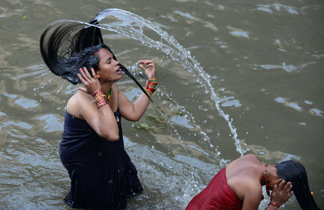 Nepalese Hindu women take a ritual bath in the Bagmati River during the Rishi Panchami festival in Kathmandu on September 18, 2015. Rishi Panchami marks the end of the three-day long Teej festival, in which married women fast and pray for the good health of their husbands to Shiva, the Hindu god of destruction, while unmarried women wish for handsome husbands and happy conjugal lives. (Photo by Prakash Mathema/AFP Photo)