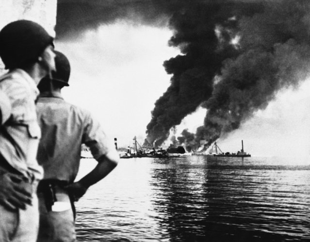 Unidentified American soldiers watch flames and smoke shoot skyward from wrecked vessels and port installations at Palermo, Sicily on September 21, 1943. This was the result of an attack by Axis dive-bombers upon the port soon after the Americans moved in. (Photo by AP Photo)