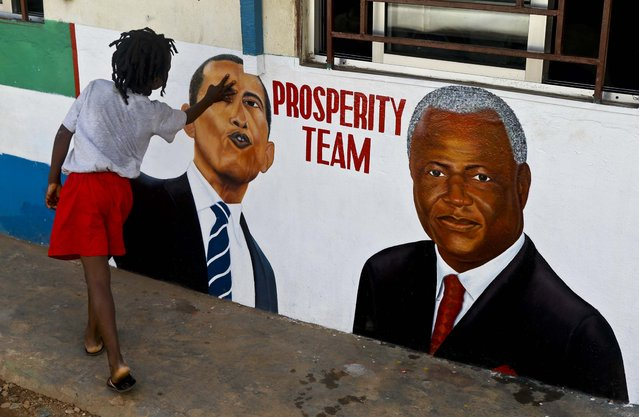A girl touches a painted picture of President Barack Obama and Sierra Leone President Ernest Bai Koroma, on the outside of a hair salon, in Freetown, Sierra Leone, November 19, 2012. (Photo by Rebecca Blackwel/Associated Press)
