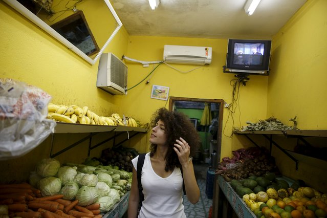 Syrian Tulin Hashemi shops for fruit at a market in Vidigal slum in Rio de Janeiro, Brazil, September 22, 2015. (Photo by Pilar Olivares/Reuters)