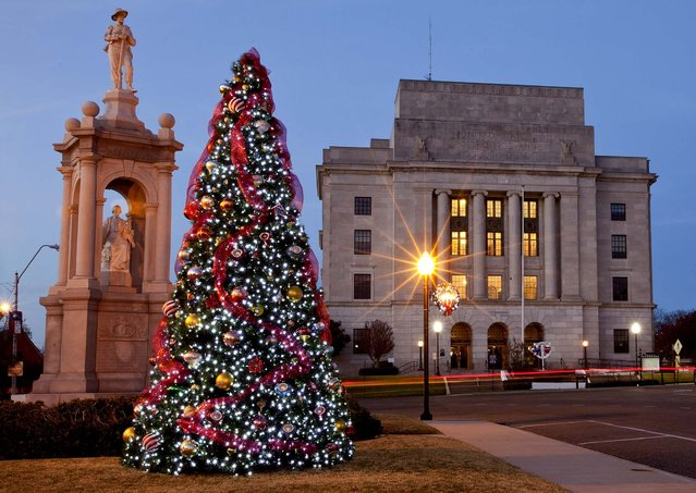 A fully decorated Christmas tree is lit on the traffic island in front of the United States Post Office along State Line Avenue in Texarkana, Texas. (Photo by Doug Strickland/The Texarkana Gazette)