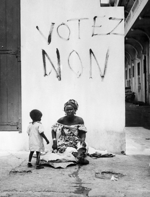 """A woman and her child are held before a slogan calling to vote """"no"""" in Dakar, french colony, on September 28, 1958, during the referendum on the new Constitution, proposed by General De Gaulle, referendum which gave birth to the Fifth Republic. The new Constitution, which reduced the power of Parliament and strengthened that of the president, who will now be elected by universal suffrage, has been approved for 82.60 per cent of the votes cast. (Photo by AFP/Getty Images)"""