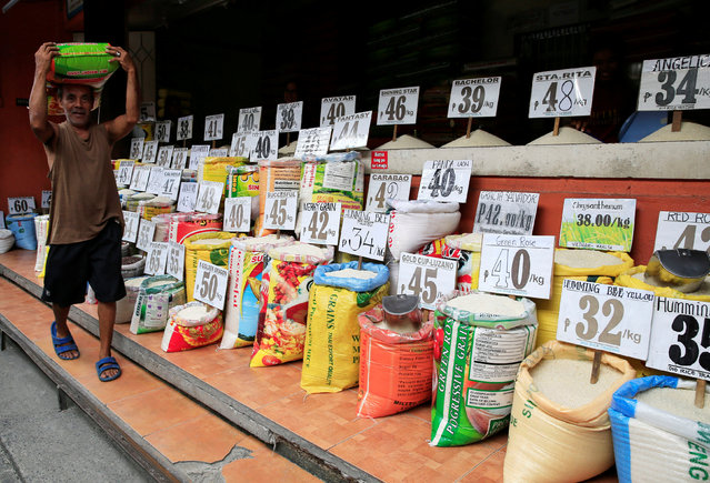 A worker carrying a sack of rice before delivering it to a customer walks past a rice store in metro Manila, Philippines  August 18, 2016. (Photo by Romeo Ranoco/Reuters)