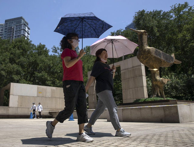 Residents wearing masks to curb the spread of the coronavirus walk past statues of birds in Beijing, China on Monday, July 6, 2020. (Photo by Ng Han Guan/AP Photo)