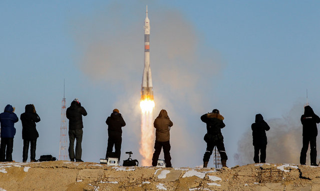 Photographers take pictures as the Soyuz MS-07 spacecraft carrying the crew of Norishige Kanai of Japan, Anton Shkaplerov of Russia and Scott Tingle of the U.S. blasts off to the International Space Station (ISS) from the launchpad at the Baikonur Cosmodrome, Kazakhstan December 17, 2017. (Photo by Shamil Zhumatov/Reuters)