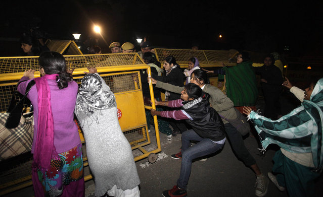 Indian women protesting against the brutal gang-rape of a woman last week attempt to remove police barricades as they try to approach the residence of Indian Home Minister Sushilkumar Shinde in New Delhi, on December 24, 2012. Authorities shut down roads in the heart of India's capital on Monday to put an end to a week of demonstrations. (Photo by Mustafa Quraishi/AP Photo)