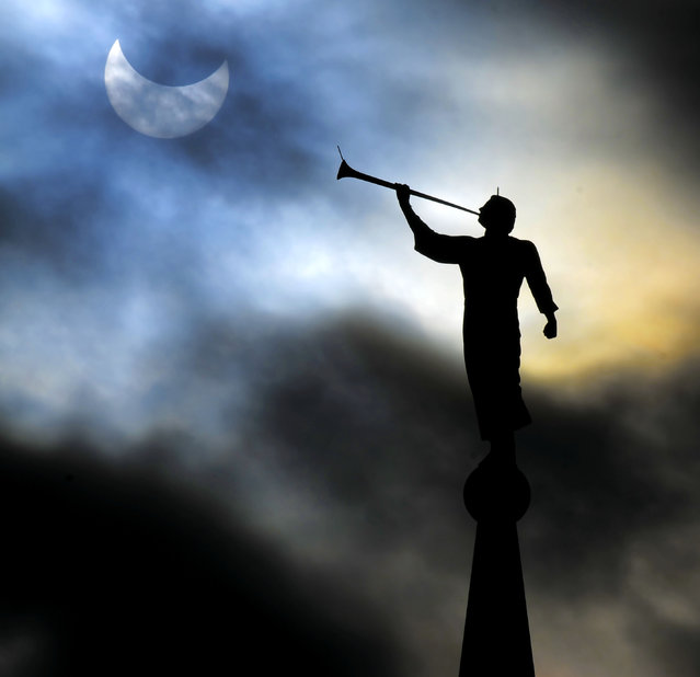 The Angel Moroni statue on the top of The Church of Jesus Christ of Latter-day Saints' temple in Brigham City, Utah, is silhouetted by a solar eclipse, Thursday, October 23, 2014. (Photo by Eli Lucero/AP Photo/The Herald Journal)