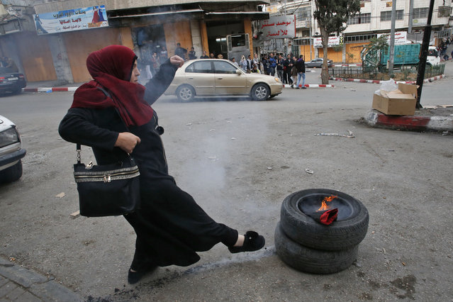 A Palestinian demonstrator kicks tyres during clashes with Israeli security forces near a checkpoint in the city centre of the West Bank town of Hebron on December 20, 2017. (Photo by Hazem Bader/AFP Photo)