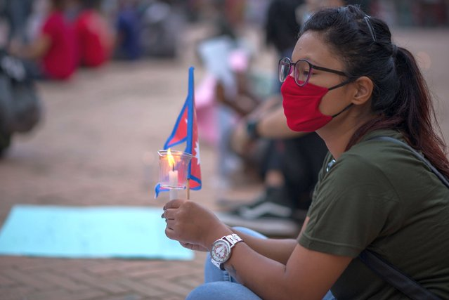 A protester sits with a candle and flag while keeping a safe distance during a demonstration on July 2, 2020 in Kathmandu, Nepal. Nepalese people have gathered to protest peacefully under covid 19 precautions, against the government's inefficiency in handling the coronavirus pandemic crisis. (Photo by Bivas Shrestha/SOPA Images/LightRocket via Getty Images)