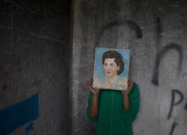 In this Wednesday, July 30, 2014 photo, a young Honduran migrant who didn't want his face to appear in photos hides behind a painting he found in a guard shack, while waiting with a group of migrants for a northbound train, in Huehuetoca, outside Mexico City. (Photo by Rebecca Blackwell/AP Photo)