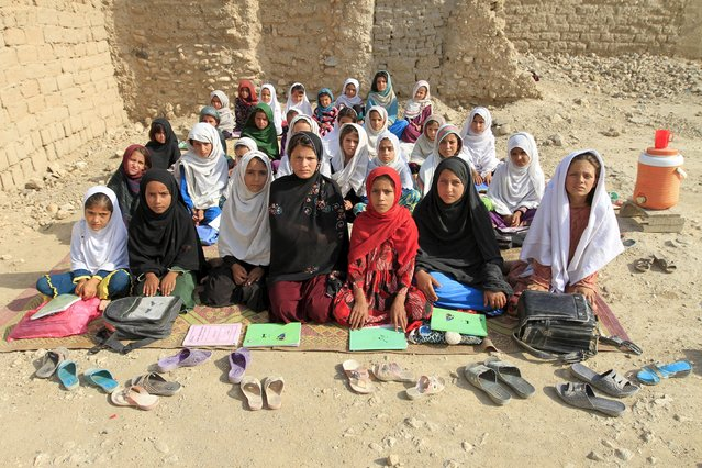 Teacher Mahajera Armani and her class of girls pose for a picture at their study open area, founded by Bangladesh Rural Advancement Committee (BRAC), outside Jalalabad city, Afghanistan September 19, 2015. (Photo by Reuters/Parwiz)