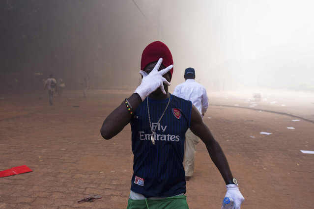 In this photo taken Thursday, October 30, 2014, a protester holds his hand over his face as he and others go on a rampage near the parliament building in Burkina Faso as people protest against their longtime President Blaise Compaore who seeks another term, in Ouagadougou, Burkina Faso. (Photo by Theo Renaut/AP Photo)