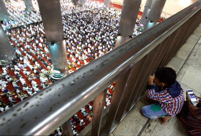A boy watches people attending prayers for the Muslim holiday of Eid Al-Adha at Istiqlal Mosque in Jakarta, Indonesia September 12, 2016. (Photo by Iqro Rinaldi/Reuters)