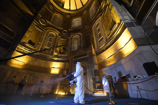 A few hours before prayers for the Islamic festival of Eid al-Adha, a municipality worker wearing protective clothing against the spread of coronavirus sprays disinfectant in the Byzantine-era Hagia Sophia, recently converted back to a mosque, in the historic Sultanahmet district of Istanbul, early Friday, July 31, 2020. This is the first Feast of Sacrifice since the onset of the coronavirus pandemic. The major Muslim holiday, at the end of the hajj pilgrimage to Mecca, is observed around the world by believers and commemorates prophet Abraham's pledge to sacrifice his son as an act of obedience to God. (Photo by Yasin Akgul/AP Photo)