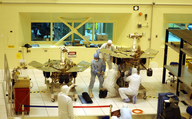 Workers put final touches to the two new Mars exploration rovers at NASA's Jet Propulsion Laboratory, on February 10, 2003 in Pasadena, California. The identical robotic explorers will search for evidence of liquid water in two separate areas of the red planet. (Photo by David McNew/The Atlantic)