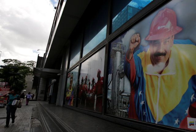 A woman walks past an image of Venezuelan President Nicolas Maduro outside a building in Caracas, Venezuela September 8, 2016. (Photo by Henry Romero/Reuters)