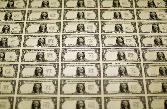 A sheet of the front side of one dollar bills is seen during production at the Bureau of Engraving and Printing in Washington November 14, 2014. (Photo by Gary Cameron/Reuters)