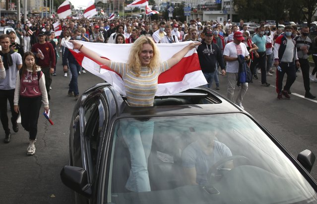 A woman standing in a car, waves an old Belarusian national flag, during a Belarusian opposition supporters' rally protesting the official presidential election results in Minsk, Belarus, Sunday, September 13, 2020. (Photo by TUT.by via AP Photo)