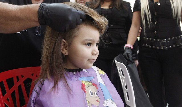 Hair stylist Marcelo Avatte fits a natural hair wig on Alexandra Munoz, 5, who lost her hair due to chemotherapy for a brain tumor, in the cancer ward of the Luis Calvo Mackenna Hospital in Santiago, October 23, 2014. (Photo by Rodrigo Garrido/Reuters)
