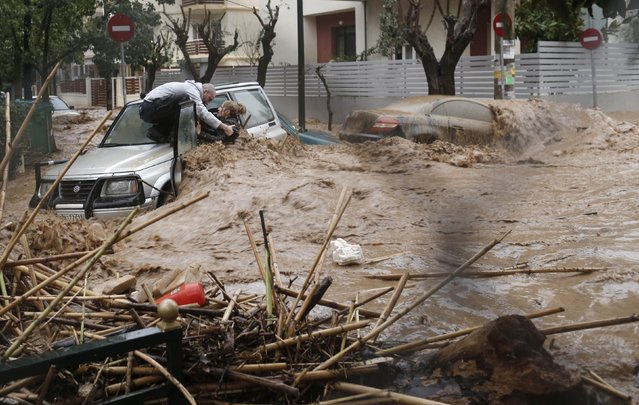 A woman is rescued from flood waters by a resident standing on top of her car during heavy rain in Chalandri suburb north of Athens, Greece, February 22, 2013. (Photo by John Kolesidis/Reuters)