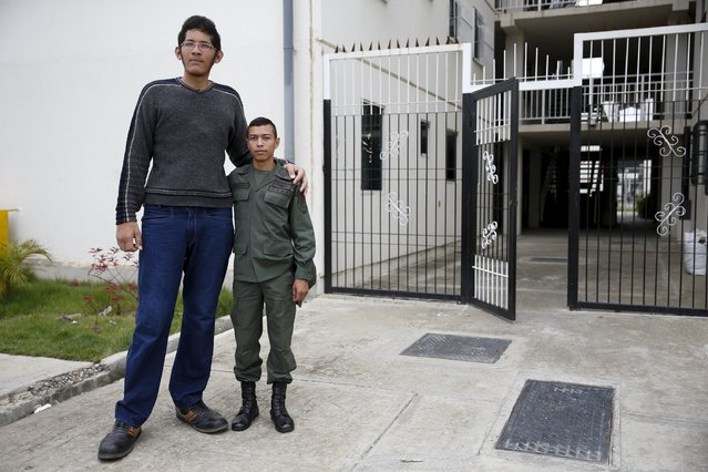 Jeison Rodriguez (L), 19, the living person with the largest feet in the world, poses for a picture with his older brother Wilmer, 24, outside their house in Maracay, Venezuela, October 14, 2015. (Photo by Carlos Garcia Rawlins/Reuters)