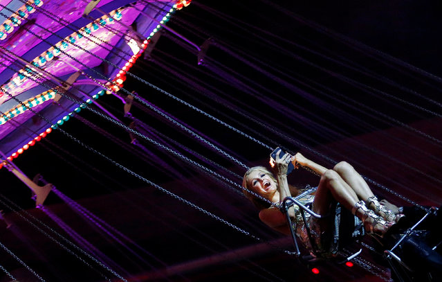 Model Paris Hilton smiles as she rides on a carousel during a party after the Philipp Plein fashion show during Milan Fashion Week Spring/Summer 2017 in Milan, Italy, September 21, 2016. (Photo by Alessandro Garofalo/Reuters)