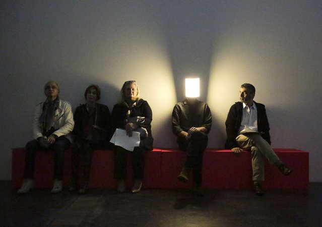 """A man in an LED light mask (2nd R) performs the live art piece """"Player"""" as he sits among visitors during the press preview of French artist Pierre Huyghe's first major retrospective at the Los Angeles County Museum of Art (LACMA) in Los Angeles, California November 19, 2014. (Photo by Jason Redmond/Reuters)"""