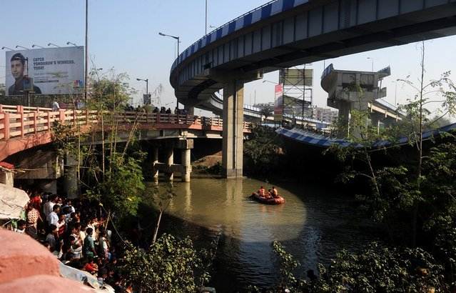 Indian onlookers watch as rescue personnel search waters near the collapsed portion of the flyover in Kolkata on March 3, 2013. A huge portion of a flyover on the eastern side of the Indian metropolis collapsed leaving three persons injured, the flyover connects the airport with Eastern Metropolitan Bypass and the eastern and southern suburbs.   As the debris fell into a canal running below the flyover, it took down a truck the driver and two others were rescued from the canal by fire-brigade personnel and locals. (Photo by Dibyangshu Sarkar/AFP Photo)