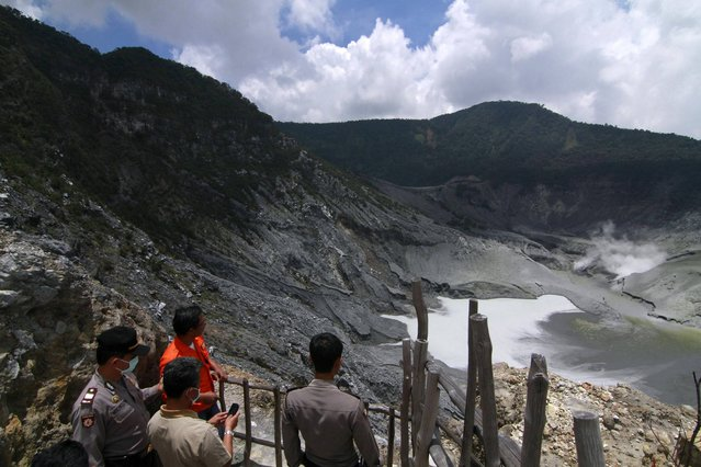 Indonesian officials examine the crater of Tangkuban Perahu volcano in Subang, West Java, Indonesia, Thursday, March 7, 2013. Indonesian authorities are closely monitoring the smoking volcano popular with tourists on Java island and are urging everyone to stay off the mountain's slope after it spewed smoke and ash nearly 500 meters (1,640 feet) into the air since Monday. Scientists have put it on the second-highest alert level. (Photoby Kusumadireza/AP Photo)