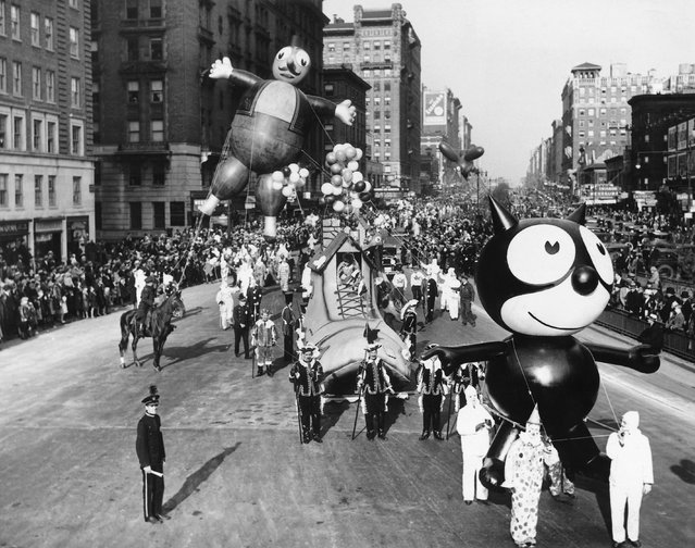 A Felix the Cat balloon and other parade floats and balloons are led down Broadway during the annual Macy's Thanksgiving Day Parade; ca. 1900s, Broadway, Manhattan, New York City, New York State, USA. (Photo by Underwood & Underwood/Corbis)