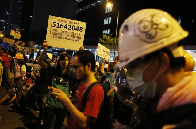 A woman holds a board with a contact number people can seek help from in case they are arrested outside the chief executive office during a pro-democracy rally in Hong Kong, November 30, 2014. (Photo by Bobby Yip/Reuters)