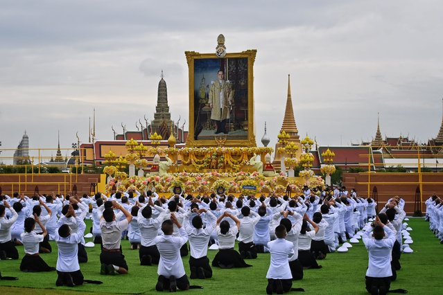 Students pay their respects before the portrait of the late Thai King Bhumibol Adulyadej, during official ceremony marking the fourth anniversary of his death, in front of the Grand Palace in Bangkok on October 13, 2020. (Photo by Lillian Suwanrumpha/AFP Photo)