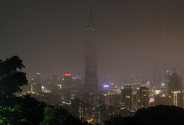 The Taipei 101 Building is seen darkened during the Earth Hour in Taipei, Taiwan, Saturday, March 23, 2013. Organised by the World Wide Fund for Nature, earth hour is observed every year to create awareness about conservation of energy and climate change. Around the world, people and organisations will be turning their lights off from 8:30 to 9:30 pm local time. (Photo by Chiang Ying-ying/AP Photo)