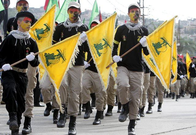 Lebanon's Hezbollah scouts carry their parties flag while marching at the funeral of three Hezbollah fighters who were killed while fighting alongside Syrian army forces in Syria in Nabatieh town, southern Lebanon, October 27, 2015. (Photo by Ali Hashisho/Reuters)