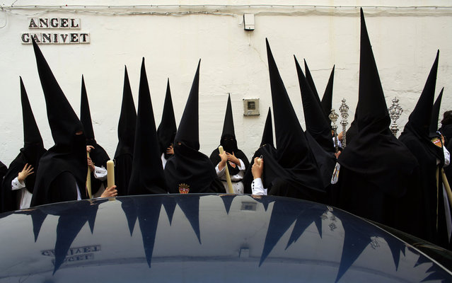 """Penitents wait before taking part in the procession of """"Santa Genoveva"""" brotherhood during Holy Week in the Andalusian capital of Seville, southern Spain, March 25, 2013. Hundreds of Easter processions take place around the clock in Spain during Holy Week, drawing thousands of visitors. (Photo by Marcelo del Pozo/Reuters)"""