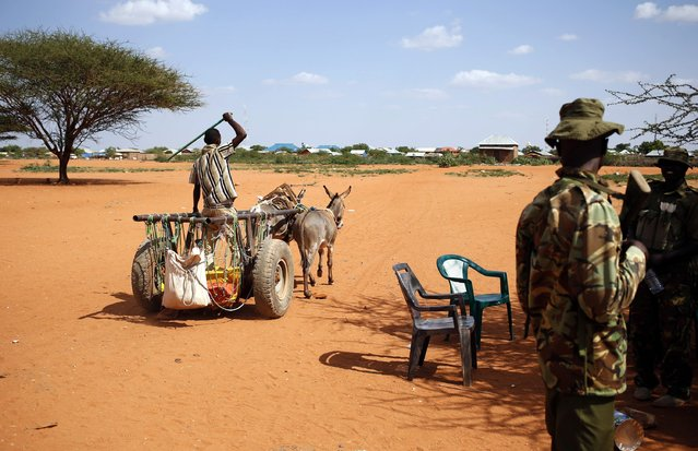 A man rides in a donkey cart past Kenya policemen as he crosses from Kenya into Somalia at the border town of Mandera December 5, 2014. Somali al Shabaab Islamist militants killed 36 non-Muslim workers at a quarry in Mandera, northeast Kenya on Tuesday, prompting the president to sweep out his top security officials in order to tackle a relentless wave of violence. (Photo by Goran Tomasevic/Reuters)