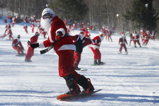 Skiers and snowboarders dressed as Santa Claus participate in a charity run down a slope at Sunday River Ski Resort in Newry, Maine December 7, 2014. Organizers say 250 skiing Santas raised $2700 for charity at the event. (Photo by Brian Snyder/Reuters)