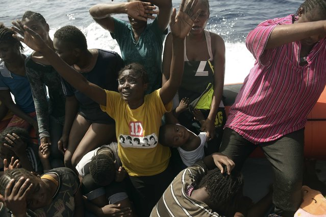 Migrants react as they are being rescued by members of Proactiva Open Arms NGO in the Mediterranean Sea, some 12 nautical miles north of Libya, on October 4, 2016. At least 1,800 migrants were rescued off the Libyan coast, the Italian coastguard announced, adding that similar operations were underway around 15 other overloaded vessels. (Photo by Aris Messinis/AFP Photo)