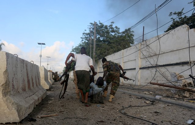 Somali soldiers evacuate their colleague who was wounded during an exchange of fire with Islamist al Shabaab gunmen outside a hotel in Somalia's capital Mogadishu, November 1, 2015.  Two bombs ripped into a hotel in the Somali capital on Sunday and security forces fought Islamist al Shabaab gunmen who stormed inside the building for hours afterwards, police and witnesses said. (Photo by Feisal Omar/Reuters)
