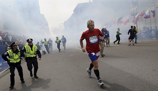A Boston Marathon competitor and Boston police run from the area of an explosion near the finish line in Boston, Monday, April 15, 2013. (Photo by Ken McGagh/AP Photo/MetroWest Daily News)