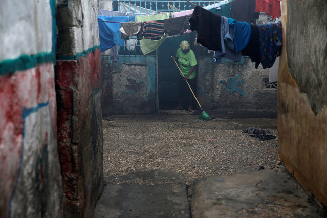 A woman cleans her house after Hurricane Matthew passes Cite-Soleil in Port-au-Prince, Haiti, October 5, 2016. (Photo by Carlos Garcia Rawlins/Reuters)