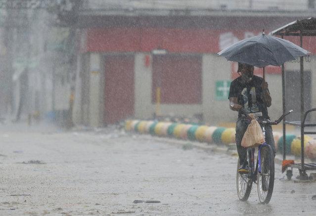 A man rides his bicycle under the rain brought by Hurricane Iota, in La Lima, Honduras, Tuesday, November 17, 2020. (Photo by Delmer Martinez/AP Photo)