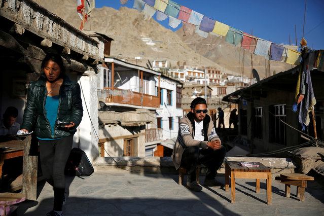 """Travel agent, Stanton Othsil, 29, sits in the sun in Leh, the largest town in the region of Ladakh, nestled high in the Indian Himalayas, India September 29, 2016. When asked how living in the world's fastest growing major economy had affected life, Othsil said: """"More tourists are coming now, especially Indians who are spending more money"""". (Photo by Cathal McNaughton/Reuters)"""