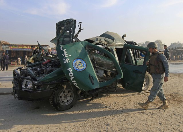An Afghan policeman inspects the wreckage of a police car at the site of a bomb explosion in Jalalabad  December 17, 2014. (Photo by Reuters/Parwiz)