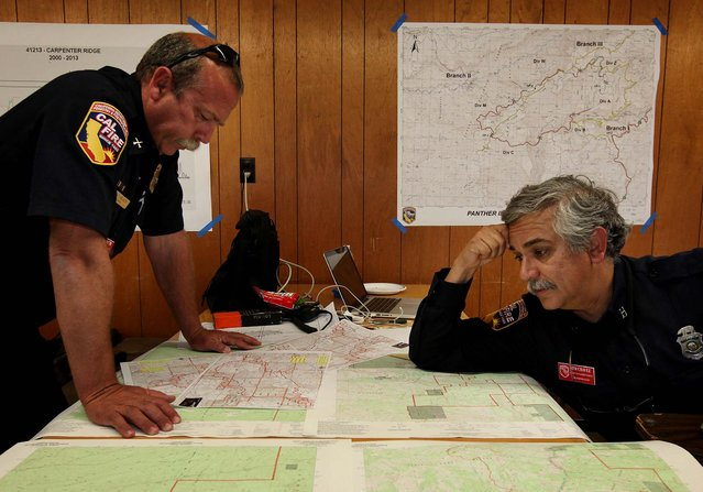 Cal Fire Planning Section Chief Steve Beach and Fire Analyst Behavior Capt. Tim Chavez, both from Riverside, look over incident maps of the Panther Fire at the Incident Command post in Chico. (Photo by Jason Halley/The Chico Enterprise-Record)