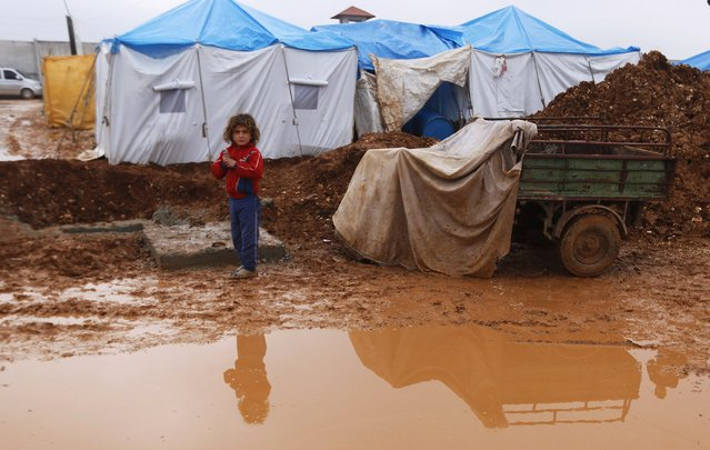 An internally displaced girl stands near a puddle of rain at the Bab Al-Salam refugee camp in Azaz, near the Syrian-Turkish border December 28, 2014. (Photo by Hosam Katan/Reuters)