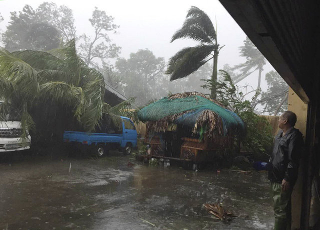 A man takes cover as strong winds and rain topple trees while Typhoon Haima lashes Narvacan, Ilocos Sur, northern Philippines on Thursday October 20, 2016. Super Typhoon Haima slammed into the northeastern Philippine coast late Wednesday with ferocious winds and rain that rekindled fears and memories from the catastrophe wrought by Typhoon Haiyan in 2013. (Photo by Bullit Marquez/AP Photo)