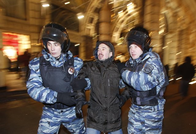 Police officers detain a protester during an unsanctioned protest in Moscow, Russia, Tuesday, December 30, 2014. The unsanctioned protest came hours after Alexei Navalny was found guilty of fraud and given a suspended sentence. Navalny, who has been under house arrest since February, is accused of breaking the terms of his house arrest to attend the rally and was detained by police as he approached the site of the protest. (Photo by Denis Tyrin/AP Photo)