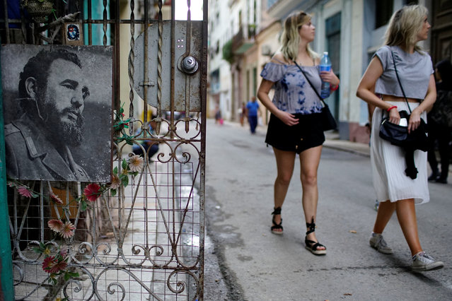Tourists walk past an image of Cuba's late president Fidel Castro in downtown Havana, Cuba, November 11, 2017. (Photo by Alexandre Meneghini/Reuters)