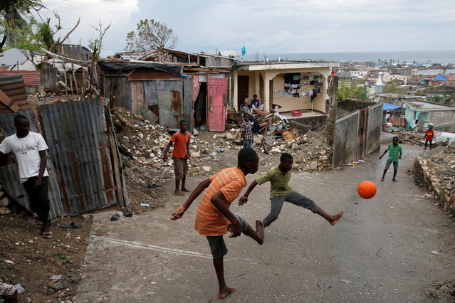 People play soccer on a street next to destroyed houses after Hurricane Matthew hit Jeremie, Haiti, October 19, 2016. (Photo by Carlos Garcia Rawlins/Reuters)